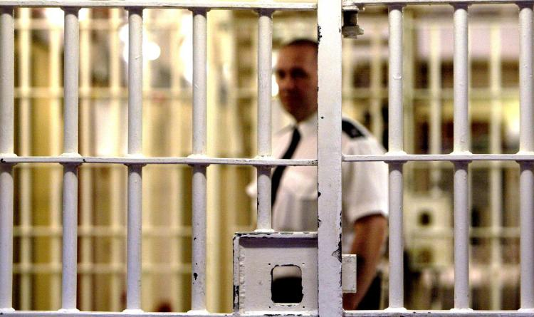 prison-warden-stands-front-cell